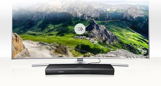 Telewizor SUHD z ekranem podzielonym na pół. Po jego lewej stronie widoczny obraz bez zastosowania technologii UHD Upscaling, po prawej – po jej zastosowaniu. Do telewizora podłączony jest odtwarzacz UHD Blu-ray K8500.